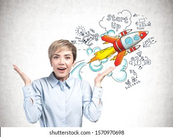 Astonished young businesswoman standing near concrete wall with colorful startup sketch drawn on it. Concept of new project