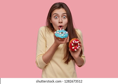 Astonished young cute European woman birtes sparkled delicious doughnut, keeps eyes wide opened, dressed in yellow sweater, has tasty snack, isolated over pink background. Sweet dish, nutrition