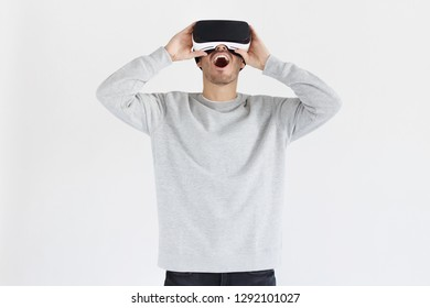 ca3b9d3fa5a Astonished young man experiencing virtual reality while using VR headset  for entertaining. People