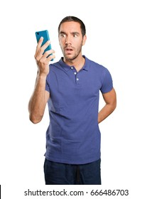 Astonished young man using a mobile phone on white background