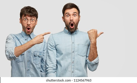 Astonished young men with scared expressions, dressed in fashionable clothing, point aside, show something unbelievable, blank space for your advertisement or promotional text. Uhg, that`s awful!