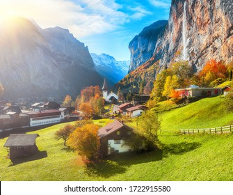 Astonishing autumn view of Lauterbrunnen valley with gorgeous Staubbach waterfall and Swiss Alps in the background.  Location: Lauterbrunnen village, Berner Oberland, Switzerland, Europe.