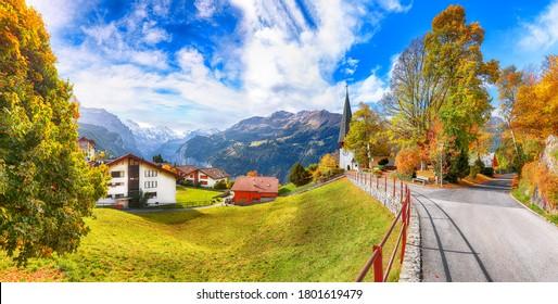 Astonishing autumn view of picturesque alpine village Wengen.  Sunny morning scene of Swiss Alps. Location: Wengen village, Berner Oberland, Switzerland, Europe.