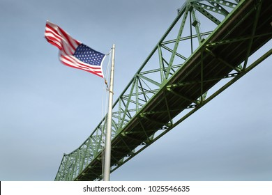Astoria Bridge, Flag, Oregon. An American flag flies beside the Astoria Megler bridge which connects Oregon and Washington over the Columbia River.