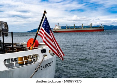 Astoria, Oregon - 8/11/2019: The stern and flag of the coast guard cutter Steadfast, and an ocean going freighter. Astoria