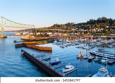 Astoria, Oregon - October 03 2017: Yachts, ships and fishing boats berthed at West Mooring Basin Marina next to the iconic Astoria Megler Bridge, commercial buildings, and homes on the coast hillside.