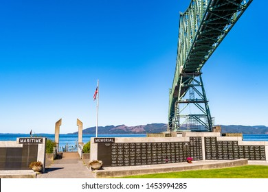 Astoria, Oregon - October 03 2017: Maritime Memorial Park and the American flag under/underneath the Astoria-Megler Bridge in Astoria in the United States which connects the city to Washington State.