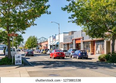 Astoria, Oregon - October 3, 2017: Cars on the street in downtown Astoria with Astoria-Megler Bridge in the background