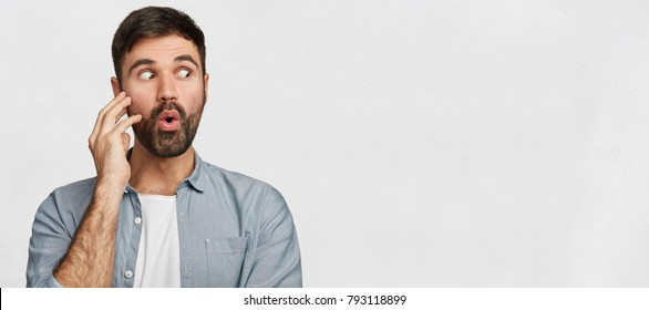 Astounded brunet young handsome male has stubble looks with shocked expression aside, notices something strange on blank white copy space, area for your advertising content and promotional text.