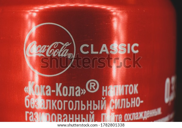 Astrakhan, Russia, 22 jul. 2020: Coca-Cola Classic drink with reflections of lights garland. Popular Soda pop side view of aluminium can with brand name in english and russian lang.