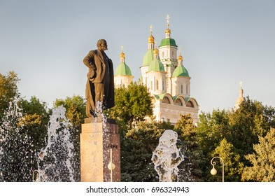 """Astrakhan, Russia, a monument to Lenin and the Assumption Cathedral on a summer evening. The inscription on the monument -""""Lenin""""."""