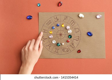 Astrological horoscope with birthstones and female hand on color background