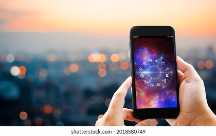 Astrological zodiac horoscope Mobile application concept.Man hands holding mobile phone on blurred city as background.element of this image furnished by NASA