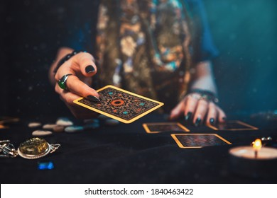 Astrology and esotericism. The female hand of the sorceress throws a Tarot card. Close up