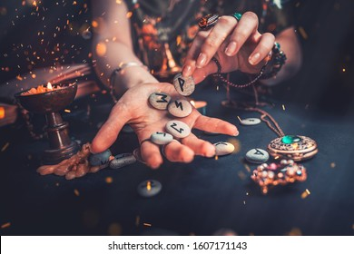 Astrology and esotericism. The witch puts the rune stones in his hand, standing next to the candle. Sparks of fire in the air. Dark background. Copy space