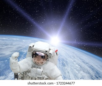 Astronaut and beautiful sunrise. The elements of this image furnished by NASA.