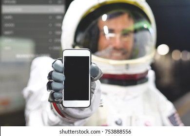 An astronaut dressed man uses the smartphone to call and send messages. The astronaut smiles while looking at the phone in his hand. Concept of: Phone Promotions, Messages and Spatial Calls.
