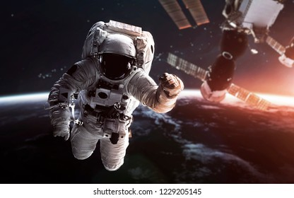 Astronaut at the Earth orbit with the Space station behind. Elements of this image furnished by NASA