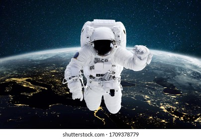 Astronaut flies in outer space against the background of the night planet Earth with light of city. Spaceman