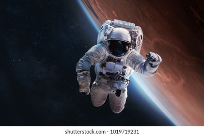 Astronaut float in outer space over of the planet Mars on the background. Elements of this image furnished by NASA