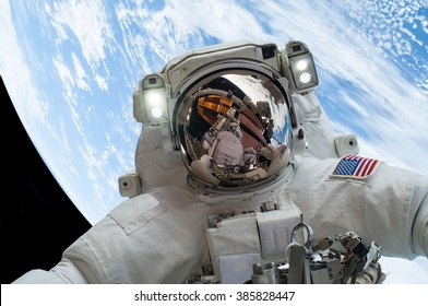 astronaut floating in space with the earth in the background [some elements courtesy of nasa]