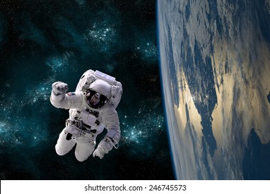 An astronaut floats above Earth. Stars provide the background.  Elements of this Image Furnished by NASA.