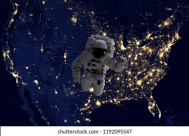 astronaut flying in open space over the USA during night, near earth.