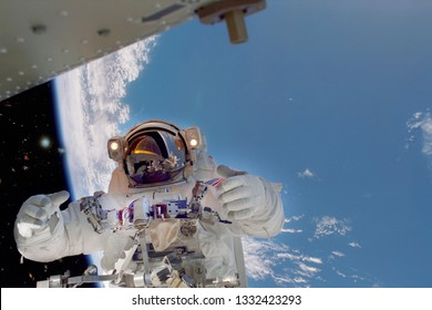 Astronaut gives push upps to the camera in outer space. Earth is on the background. ELemnts furnished by NASA.