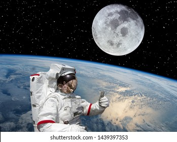 Astronaut gives thumbs up. Moon and earth on the backdrop. The elements of this image furnished by NASA.