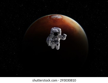 Astronaut, holding a planet Earth in hand on against of Mars. Elements of this image furnished by NASA.