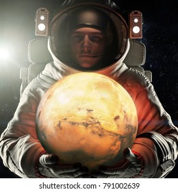 Astronaut holding the red planet of Mars. Exploration and journey to Mars concept. 3d rendering .Elements of this image furnished by NASA