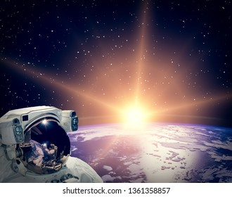 Astronaut looking at sunrise. The elements of this image furnished by NASA.