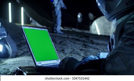 Astronaut on the Alien Planet Works on a Mock-up Green Screen Laptop. In the Background Her Crew Member and Space Habitat. Extraterrestrial Colonization Concept.