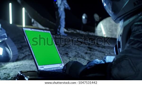 """L'astronaute sur Alien Planet travaille sur un ordinateur portable à écran vert """"Mock up"""". En toile de fond Sa membre d'équipage et Habitat spatial. Concept De Colonisation Extraterrestre."""