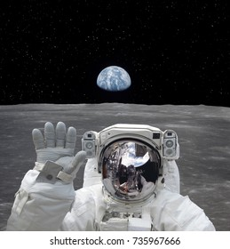 Astronaut on the moon. Waving with a hand. Earth on backdrop. Elements of this image furnished by NASA
