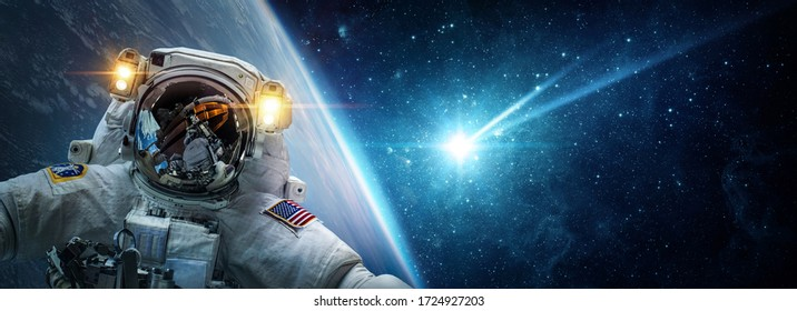 Astronaut in orbit Earth against the background of a falling meteorite, asteroid, comet. Glowing asteroid and tail of a falling comet. The concept on the theme of the apocalypse, armageddon, doomsday.