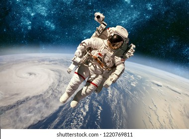 Astronaut in outer space against the backdrop of the planet earth. Typhoon over planet Earth. Elements of this image furnished by NASA.