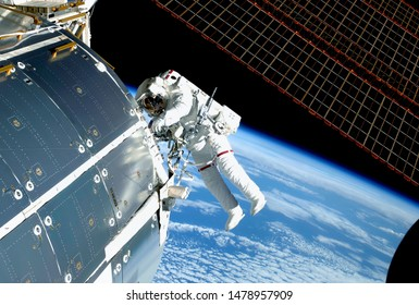 The astronaut in an outer space, at the ISS, repairs and makes experiments. Elements of this image were furnished by NASA