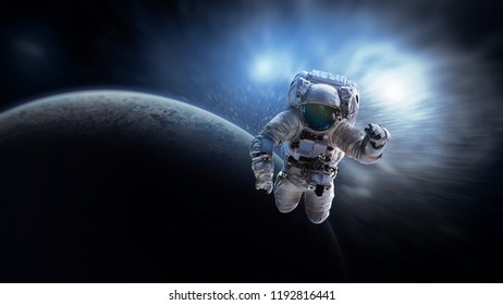 Astronaut in outer space near planet. Galaxy lights on background. Elements of this image furnished by NASA