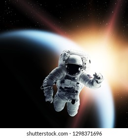 Astronaut in outer space over earth and stars background. Elements of this image furnished by NASA