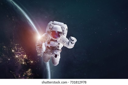 Astronaut in outer space over of the Earth with sun light. City lights on planet. Elements of this image furnished by NASA.
