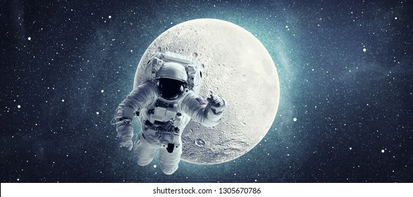 Astronaut in outer space over full moon and stars background. Elements of this image furnished by NASA