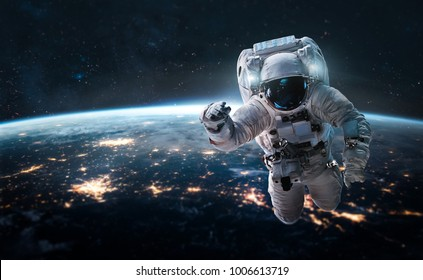 Astronaut in outer space over of the nightly Earth. City lights on background. Elements of this image furnished by NASA