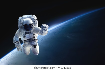 Astronaut in outer space over of the planet Earth. Blue light on background. Elements of this image furnished by NASA