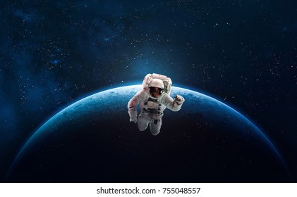 Astronaut in outer space over of the planet Earth. Colorful beautiful planet. Milky way. Blue gradient. Space wallpaper. Elements of this image furnished by NASA