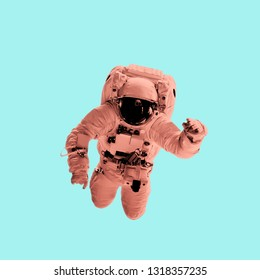 astronaut in pastel coral color on a blue background. Elements of this image furnished by NASA
