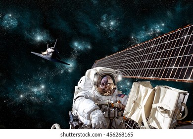 An astronaut performs work on a space station solar array while the space shuttle slowly approaches to dock. - Elements of this image furnished by NASA.