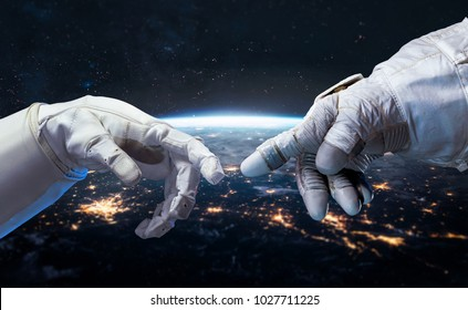 Astronaut and robot hands in the space. Earth planet on the background. Communication and technology. Cities lights. Elements of this image furnished by NASA