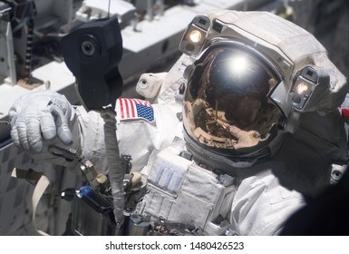 The astronaut in a space suit, in an outer space, is engaged in repair of the space station. Elements of this image were furnished by NASA