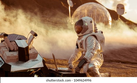 Astronaut in the Space Suit Works on Laptop, Adjusting Rover For Mars further Mars Exploration.Space Exploration Concept.First Manned Mission on Red Planet.